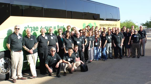"Algae Testbed Public-Private Partnership (ATP3) members gather at Arizona State University in front of a shuttle with algae images and the words ""algae + sun = fuel."" Partners from around the nation met at Arizona State University to discuss algae research and solutions."